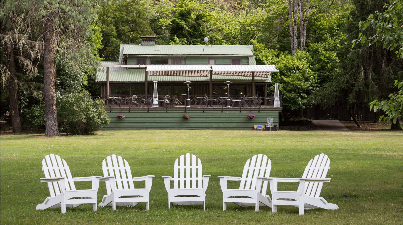 Morrisons Lodge overlooks a large green lawn with Adirondack chairs inviting guests to sit by the river.